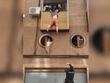 El hombre colgando de la ventana
