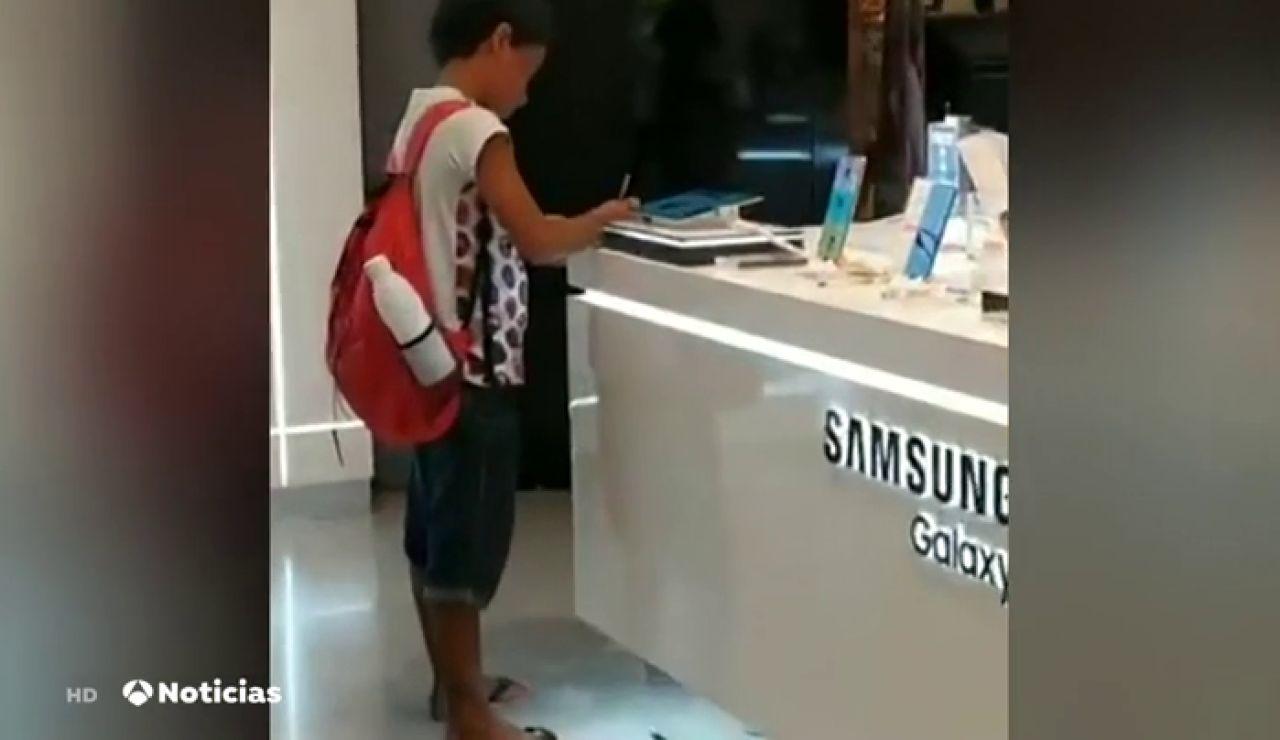 Una compañía le regala dos tablets a un niño que realizaba sus deberes en una tienda de electrónica