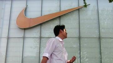 Un hombre pasa junto al letrero de una tienda Nike