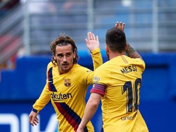 Griezmann felicita a Leo Messi durante un partido