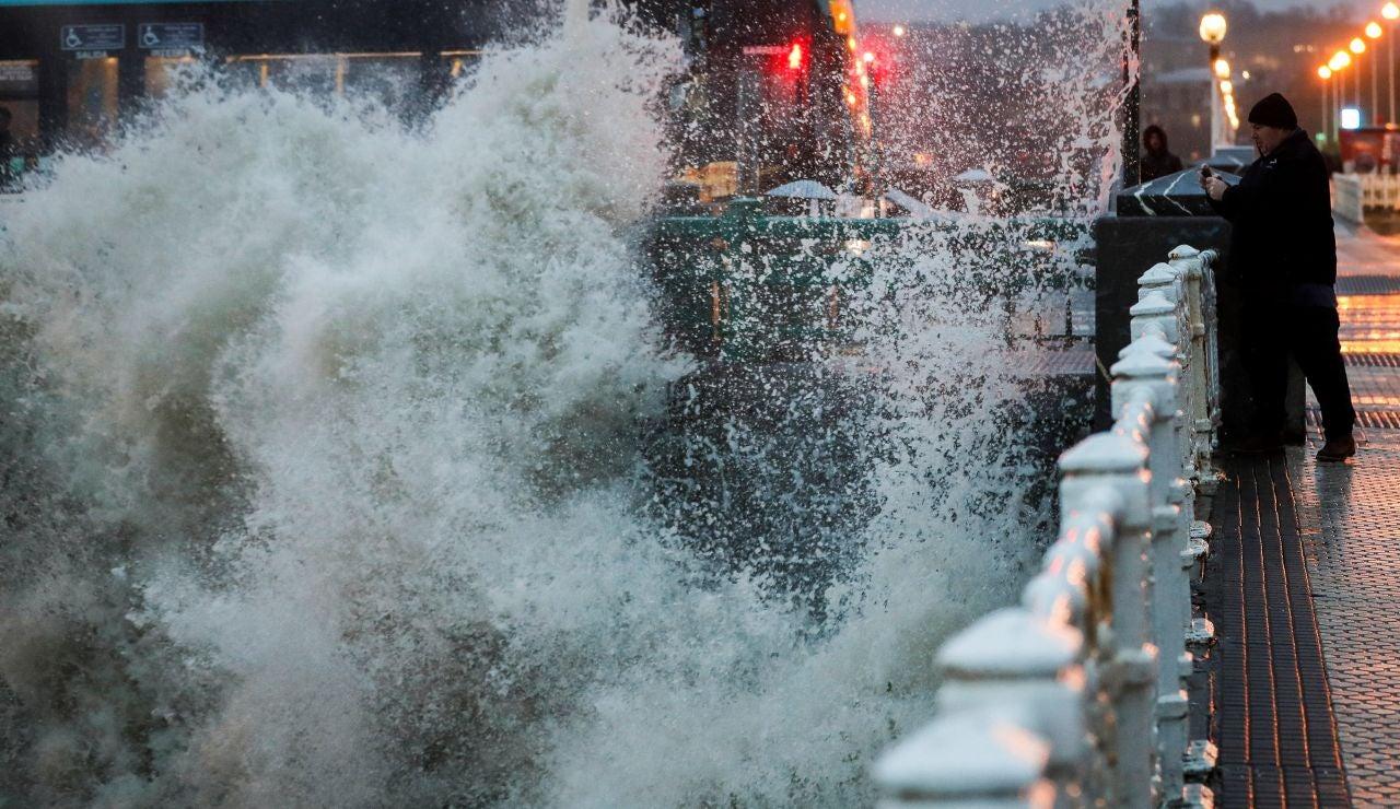 Un hombre es sorprendido por una ola en el puente del Kursaal de San Sebastián