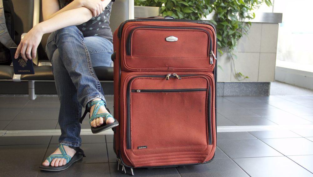 Viajero junto a su maleta