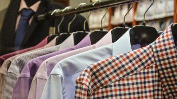 Camisas colgadas en perchas en una tienda de ropa