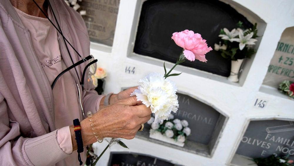 Una mujer lleva flores a un cementerio