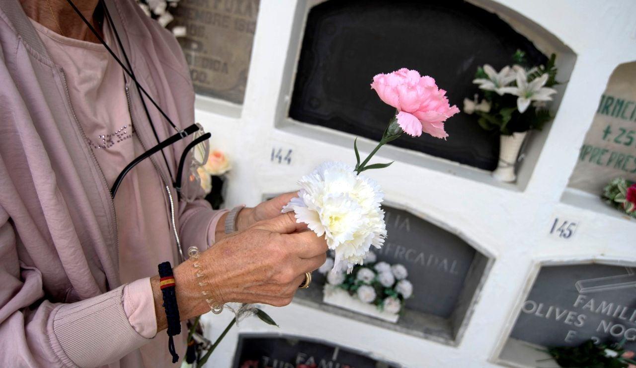 Mujer dejando flores en un cementerio