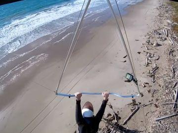 El momento en el que el hombre cae con su ala delta a la playa