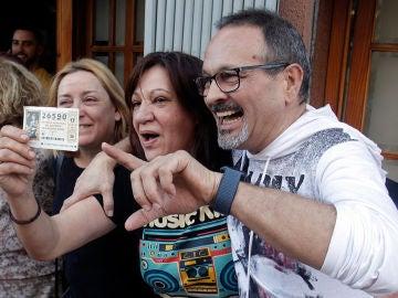 Una mujer sostiene un décimo premiado con El Gordo