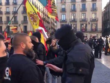 Un Mosso intenta intermedia entre los asistentes a la concentración de Vox y el grupo de CDR presentes en Sant Jaume