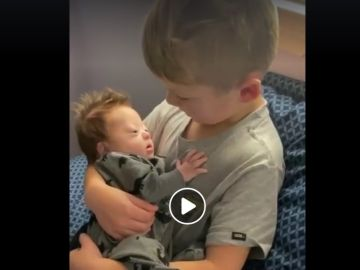 La imagen de un niño cantando a su hermano bebé con Síndrome de Down