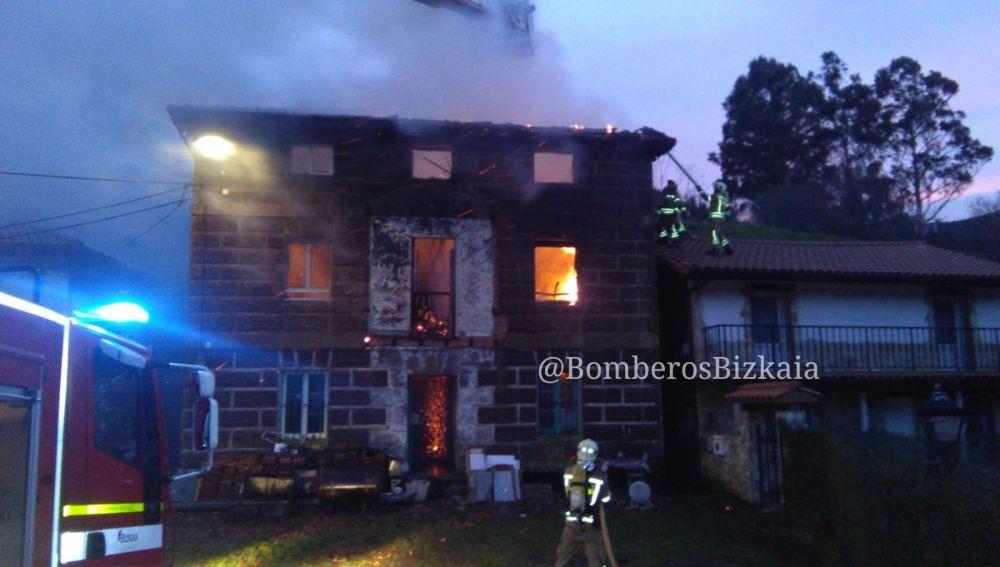 Los bomberos apagando el fuego de una casa