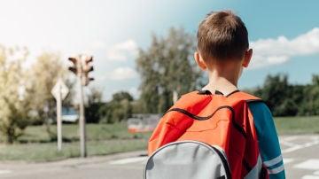 Imagen de un niño con una mochila en la calle