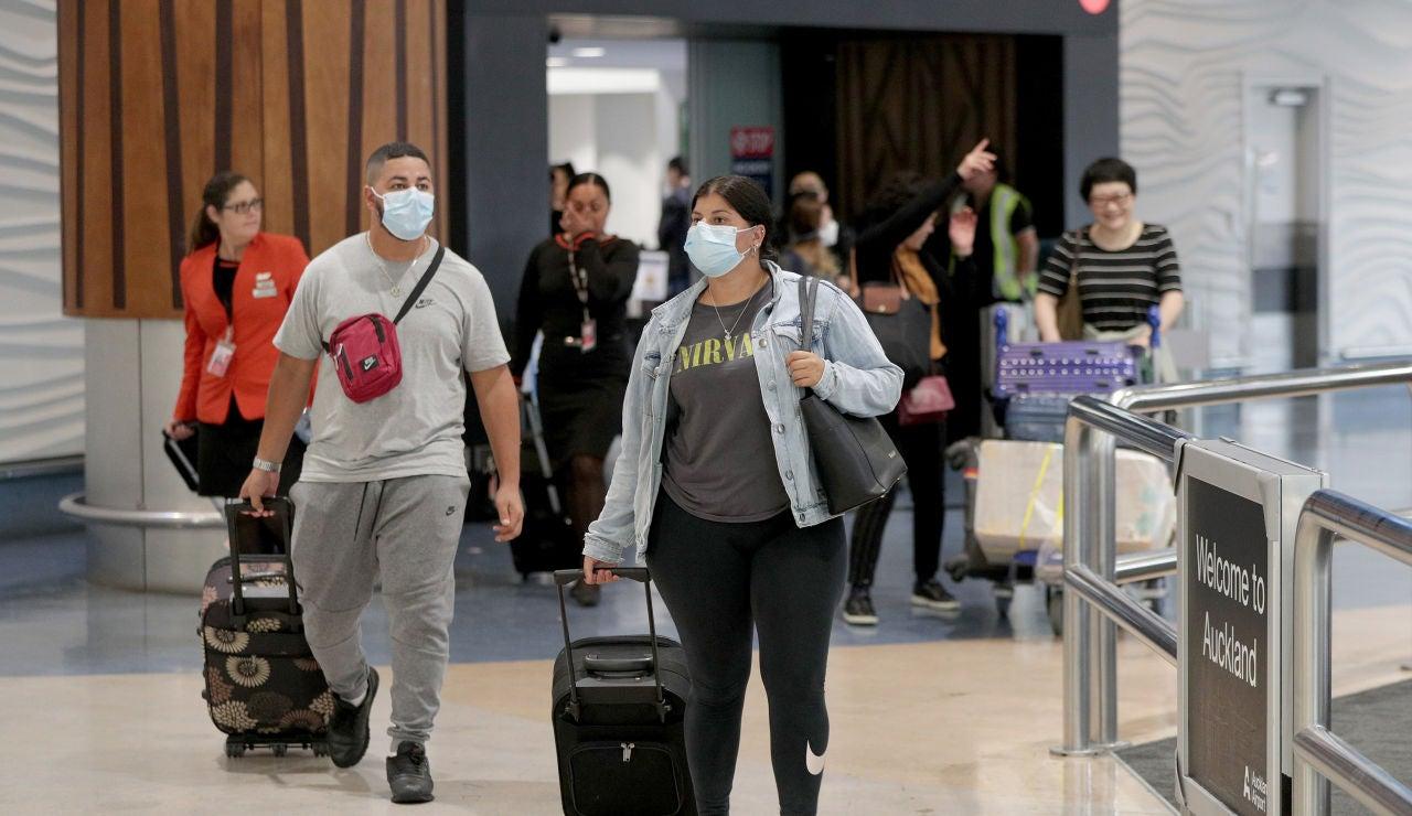 Pasajeros con máscaras en una terminal de aeropuerto