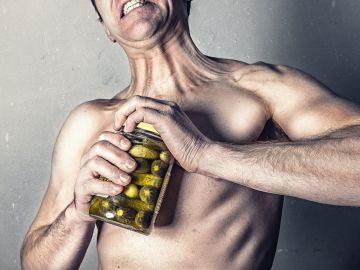 Hombre intentando abrir un frasco