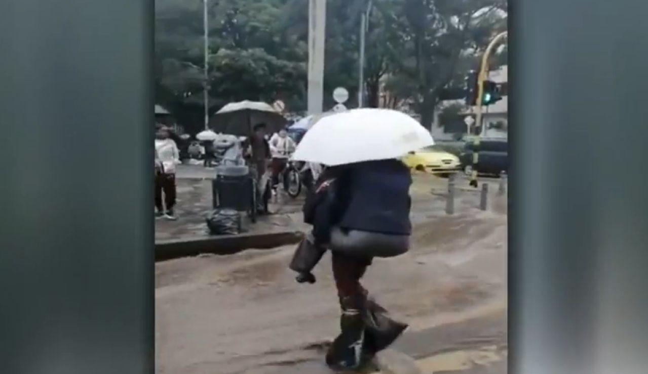 Una senadora se sube a la espalda de un hombre para cruzar la calle en Bogotá