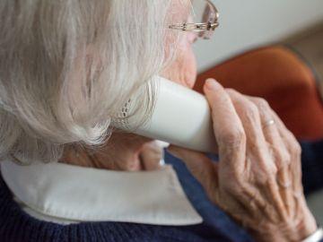 Una anciana hablando por teléfono