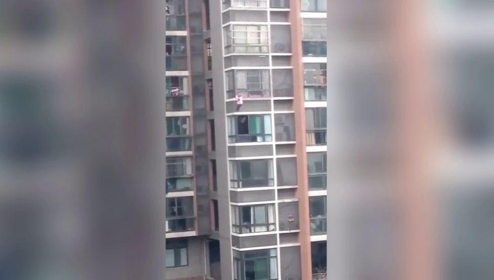 Niña colgando de un edificio
