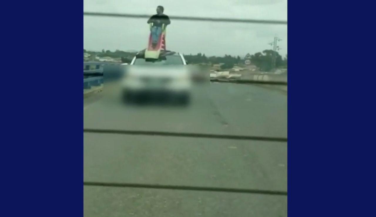 Un conductor circula con otro hombre subido en un tobogán en el techo del coche, ambos han sido detenidos