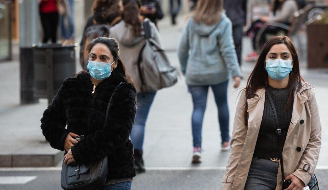 BOE Real decreto nueva normalidad: Personas con mascarillas para protegerse del coronavirus.