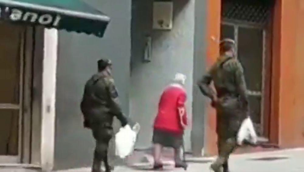 Dos militares ayudan a una anciana a llevar la compra a casa en Gijón durante la cuarentena por coronavirus