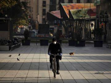 Un ciudadano en bicicleta por Barcelona en plena crisis de coronavirus