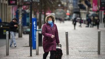 Una ciudadana pasea con una mascarilla puesta