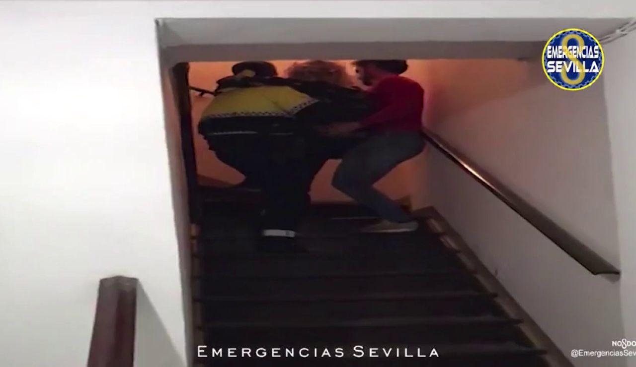 Dos policías llevan en brazos a una mujer y a su bebé recién nacido en Sevilla