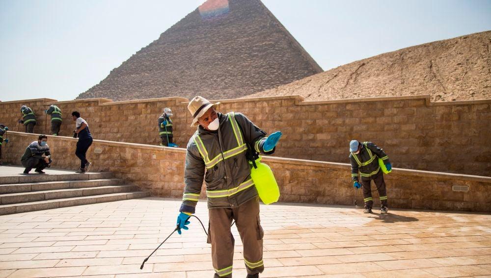 Varias personas desinfectan las inmediaciones de las pirámides de Giza en El Cairo