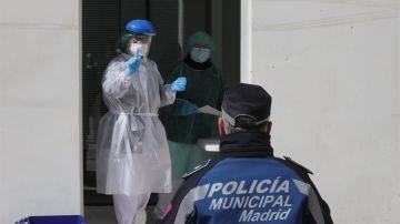 Un médico biólogo de Madrid Salud examina a un policía municipal
