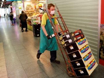 Imagen de un hombre transportando alimentos en un mercado