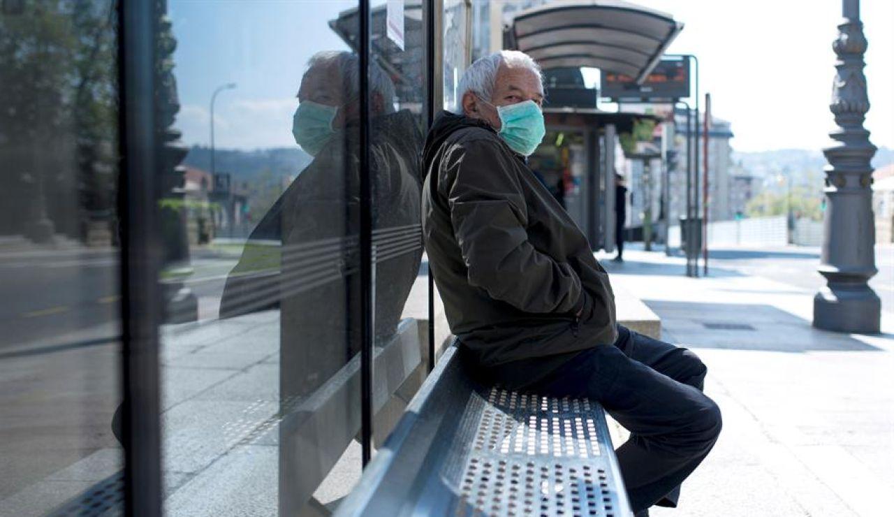 Un hombre con una mascarilla en una parada de autobús en Ourense.