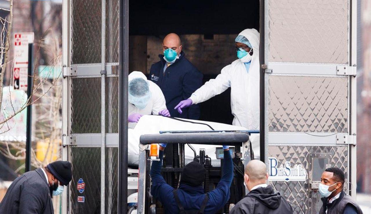 Empleados del hospital trasladan un cuerpo a un camión empleado como morgue móvil