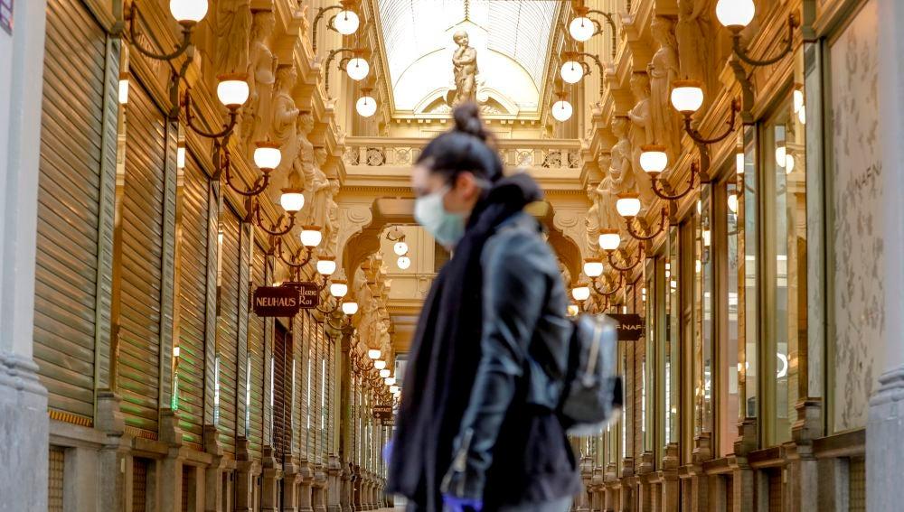 Una mujer pasea por Bruselas con mascarilla