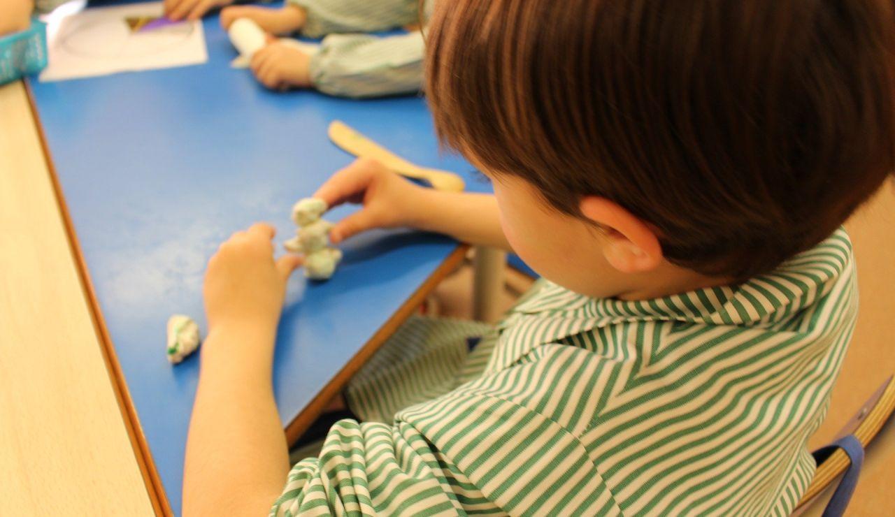 Imagen de archivo de un niño haciendo manualidades en una escuela infantil