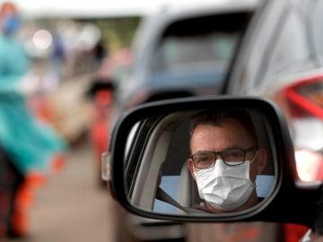 Un hombre con mascarilla en su coche