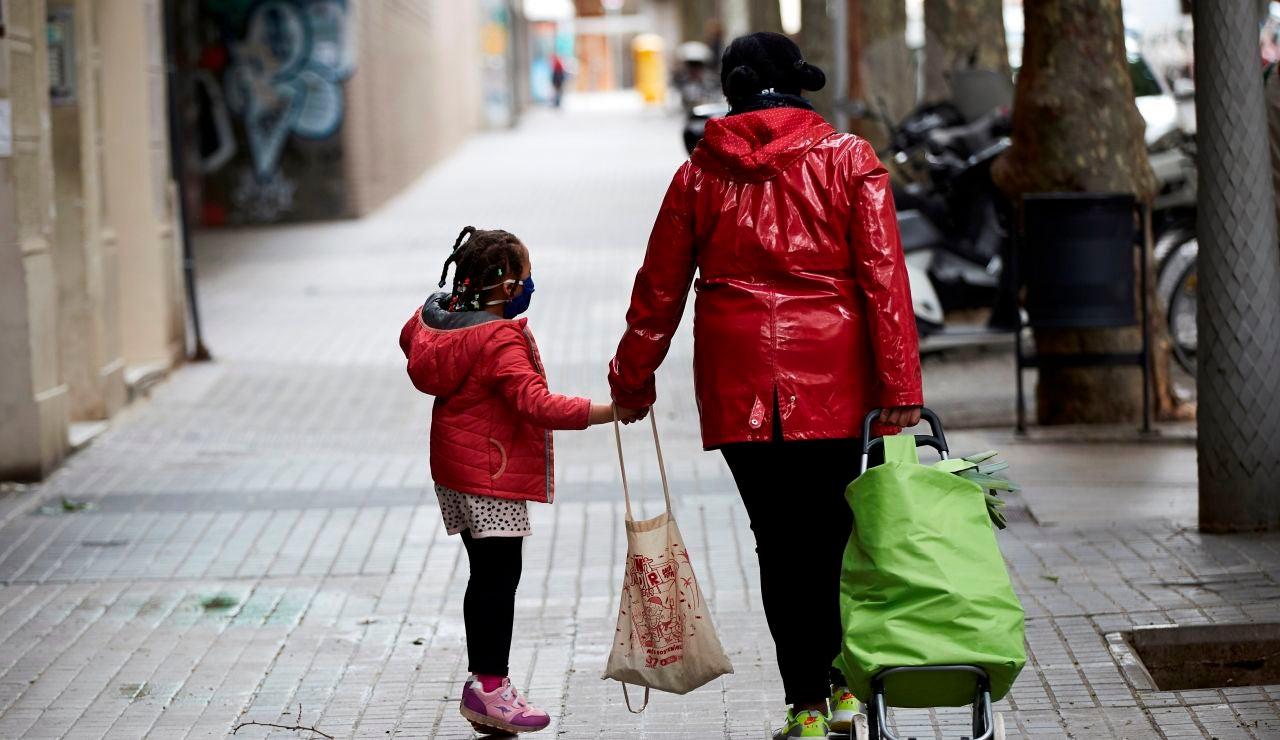 Una niña camina junto a su madre