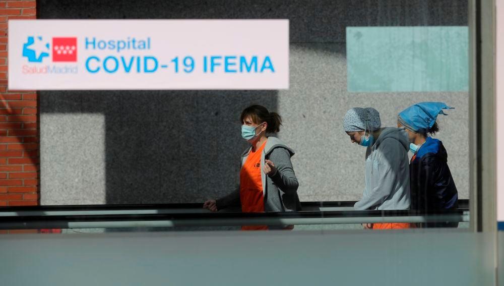 Trabajadores sanitarios caminan por una cinta desplazadora en el hospital temporal de Ifema