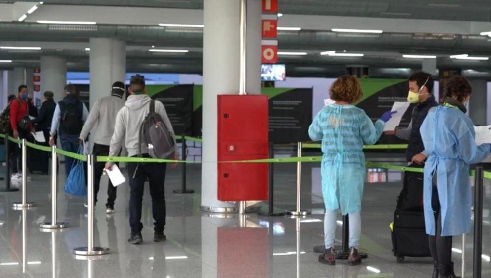 Algunos viajeros pasando el control de seguridad del Aeropuerto de Palma, con medidas especiales por el coronavirus.