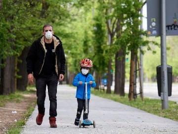 Un padre pasea con su hijo por las calles de Madrid