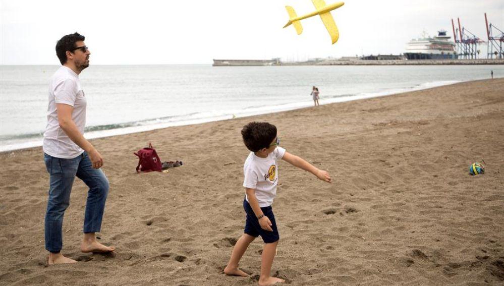 Un niño juega con su padre en la playa de la Malagueta tras 43 días de confinamiento