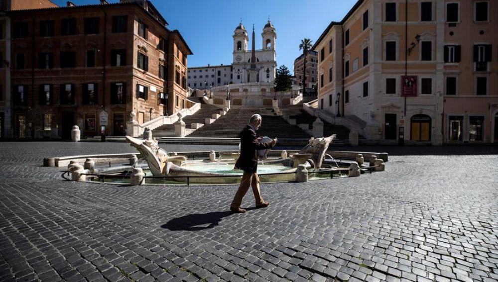 Una persona camina por la Piazza Spagna de Roma, desierta por el confinamiento por coronavirus