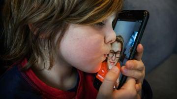 Un niño habla con su madre a través del móvil