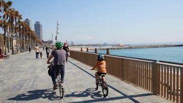 Una familia circula en bici por el paseo marítimo de Barcelona