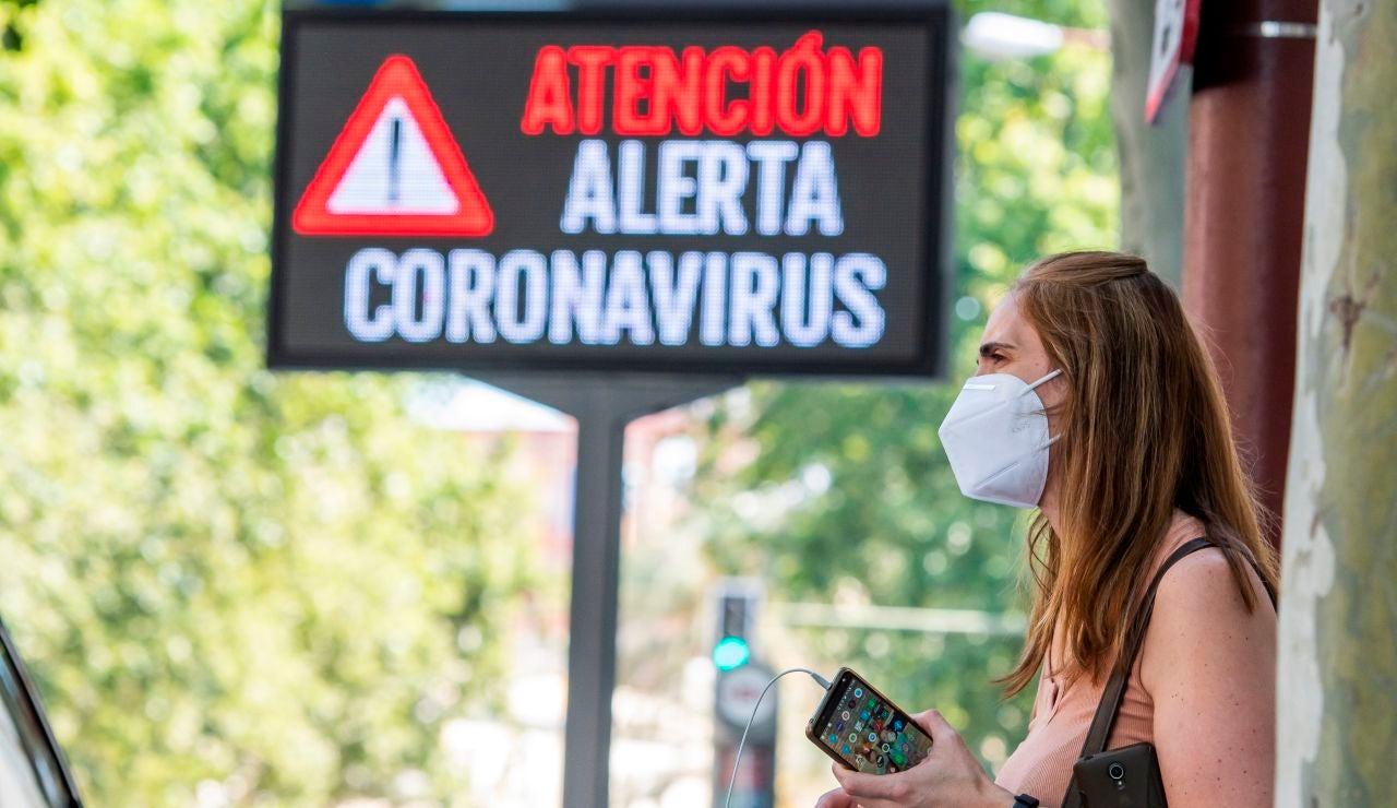 Una mujer espera el autobús junto a un panel informativo en Sevilla