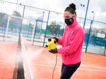 Una mujer limpia una pista del Club de Pádel Soto, en Torrejón de Ardoz