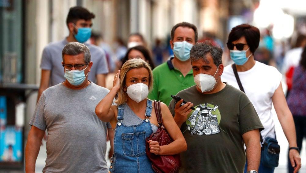 Ciudadanos pasean por la calle protegidos con mascarillas