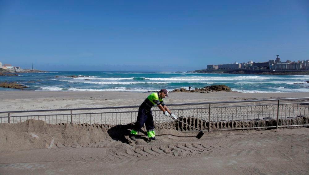 Un operario del concello de A Coruña trabaja en el acondicionando la playa de Riazor