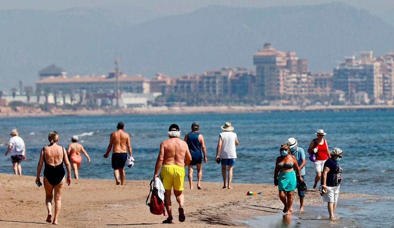 Ciudadanos pasean por la playa de Benidorm