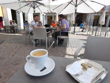 Varias personas disfrutan de la terraza de un bar.