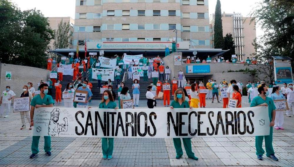 """Sanitarios del Hospital Gregorio Marañón posan con una pancarta en la que se lee """"Sanitarios necesarios"""""""