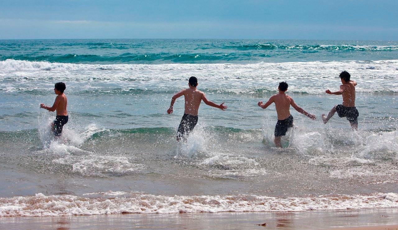 Varios jóvenes disfrutan del mar en la playa de Gandía